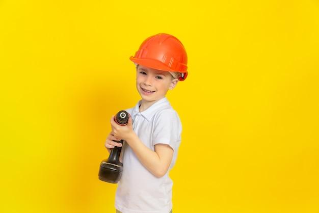 즐거운 소년이 건설에 사용되는 전기 도구를 손에 들고 있다