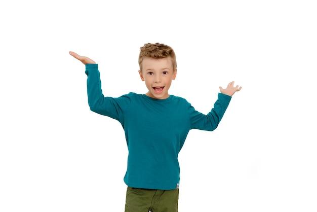 유쾌한 소년은 활짝 웃으며 팔을 위로 흔든다 프리미엄 사진