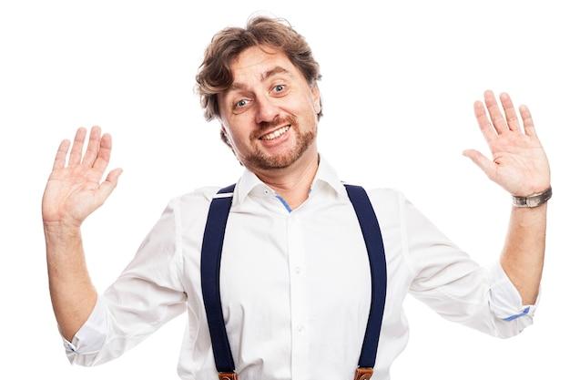 흰 셔츠와 멜빵에 빨간 머리를 가진 즐거운 남자가 손을 들었다. 흰 벽에 고립.