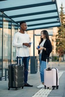 즐거운 다인종 커플이 공항 근처 버스 정류장에서 탑승권과 출발 시간을 확인합니다.