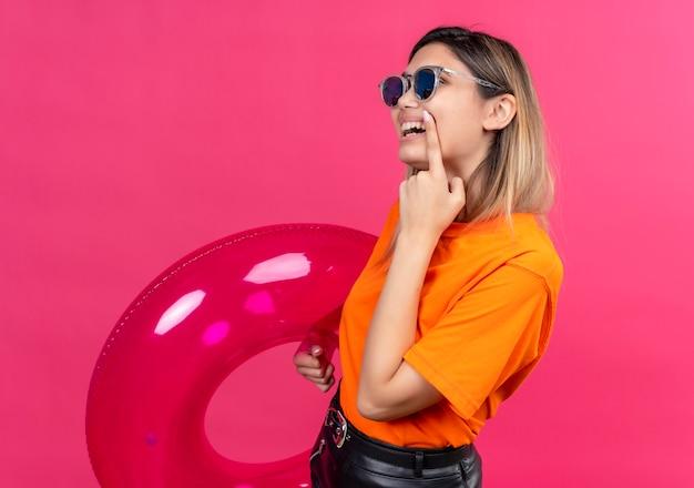 ピンクの壁にピンクのインフレータブルリングを保持しながら人差し指で彼女の口を指しているサングラスを身に着けているオレンジ色のtシャツを着た楽しいかわいい若い女性