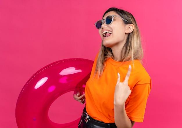ピンクの壁にピンクのインフレータブルリングを保持しながらロックジェスチャーを示すサングラスを身に着けているオレンジ色のtシャツを着た楽しいかなり若い女性