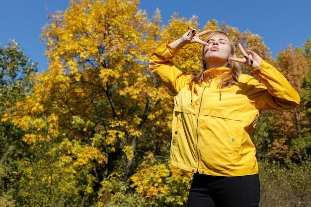 黄色い秋の木の背景にうれしそうな女性。テキスト用の空き領域。秋の気分