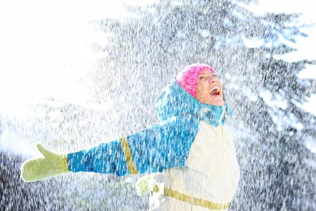 雪の中で遊ぶうれしそうな女性