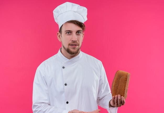ピンクの壁を見ながらパンの塊を保持している白い制服を着たうれしそうな若いひげを生やしたシェフの男
