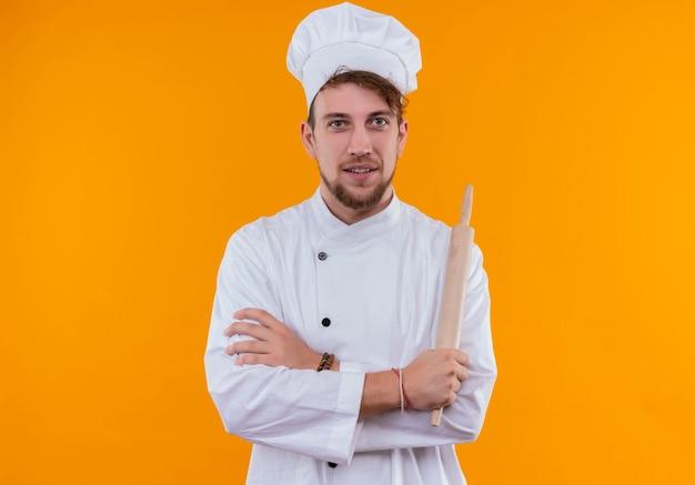 オレンジ色の壁を見ながら、手を組んで麺棒を持っている白い制服を着た楽しい若いひげを生やしたシェフの男