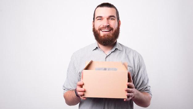 즐거운 젊은 수염 난 남자가 배달 상자를 들고 웃고 흰 벽 근처에 카메라를 찾고 있습니다