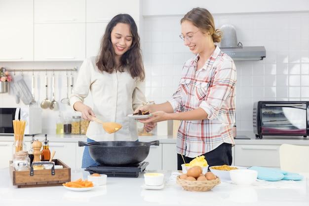 エプロンを着た楽しい若いレズビアンのペアは、フライパンとヘラを備えた木製のテーブルの後ろにある自宅のキッチンで一緒に料理をします。