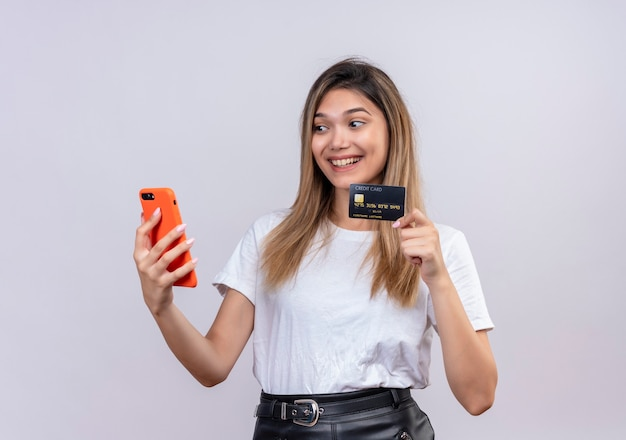 흰 벽에 휴대 전화를 보면서 신용 카드를 보여주는 흰색 티셔츠에 즐거운 젊은 여자