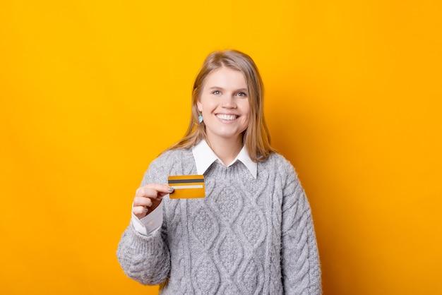 うれしそうな若い女性がクレジットカードを持っていて、見て笑っている