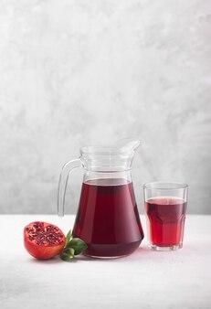 회색 배경에 신선한 석류 과일이 있는 석류 주스 한 병. 비타민과 미네랄을 함유하고 있어 헤모글로빈 증가에 도움
