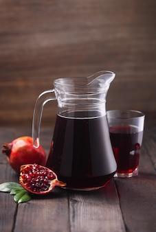나무 갈색 배경에 신선한 석류 과일과 함께 석류 주스의 용기. 비타민과 미네랄을 함유하고 있어 헤모글로빈 증가에 도움