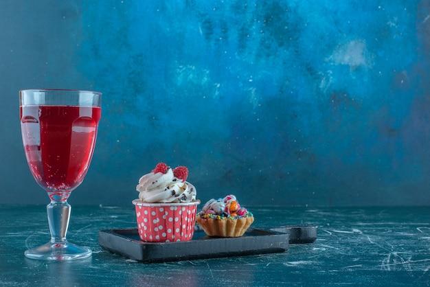 파란색 배경에 컵 케이크 옆에 주스 유리. 고품질 사진