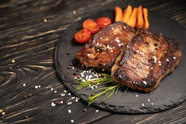 На каменной тарелке лежит сочный кусок жареного мяса с запеченными на гриле помидорами черри и морковью.