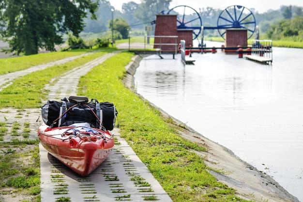 ポーランドの歴史的建造物のシーンでエルブロンスキ運河の隣にある旅行用バッグ付きのカヤック