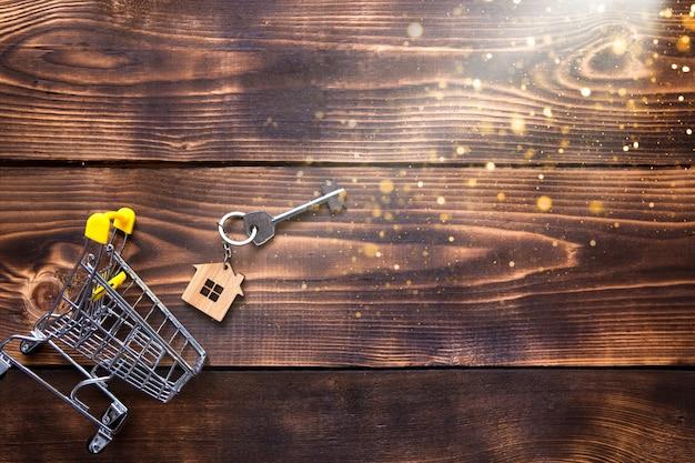 Ключ с кольцом для ключей в виде домика на деревянном фоне торчит из уменьшенной тележки супермаркета.