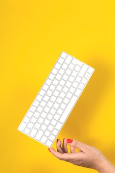 가정용 컴퓨터의 키보드가 여성의 손에 균형을 이룹니다.