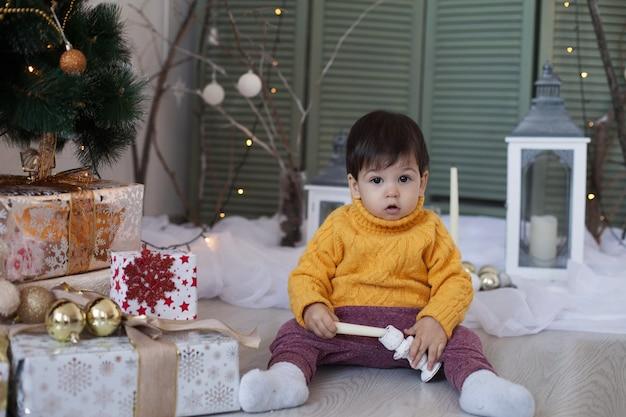 노란 스웨터를 입은 꼬마 소년이 바닥에 앉아 크리스마스 트리와 축제 인테리어 근처에서 촛불을 가지고 놀습니다.