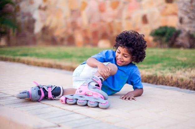Малыш мальчик на роликах упал и чувствует боль. концепция детей, отдыха и здравоохранения
