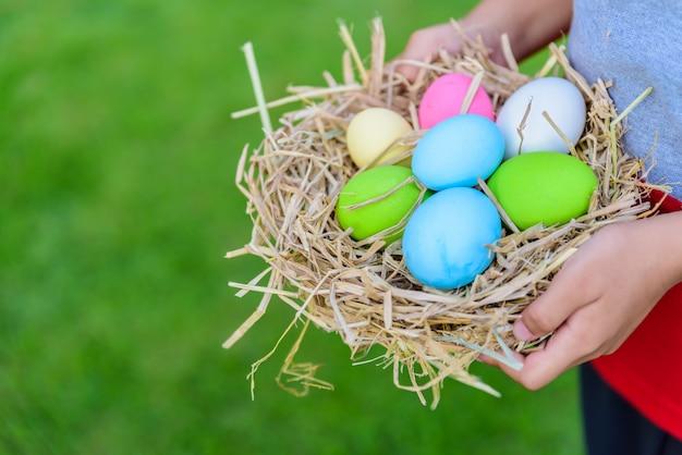 잔디 녹색 배경에 둥지에 부활절 달걀의 다채로운 들고 아이