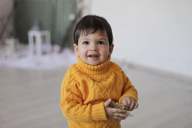노란색 스웨터를 입은 한 아이가 손과 미소에 크리스마스 골드 스타를 들고 있습니다.