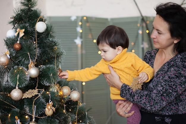 노란 스웨터를 입은 아이가 엄마 품에 앉아있는 크리스마스 트리에있는 공을 손에 넣습니다.