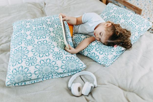 ベッドでのオンライン学習の子供、タブレットとヘッドフォンでベッドの中で少女