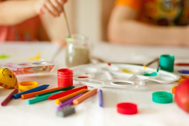 紙に色の塗料で描く子供たち。