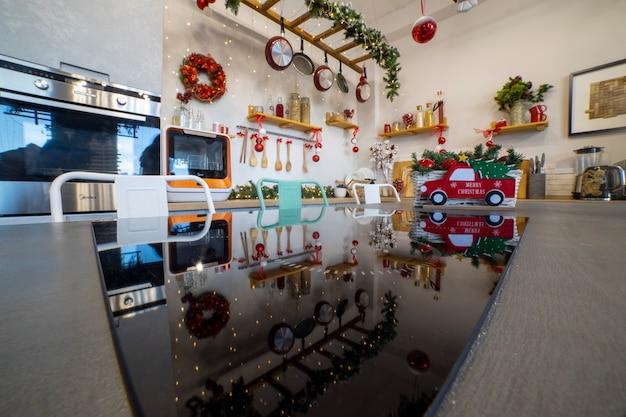家族のクリスマスのお祝いのためのキッチンのクリスマスの装飾を反映したコンロのあるキッチンアイランド....