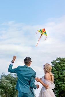 결혼식에서 연입니다. 결혼식 한 쌍이 하늘로 연을 날립니다. 신랑 신부는 결혼식 날 함께 연을 날립니다.