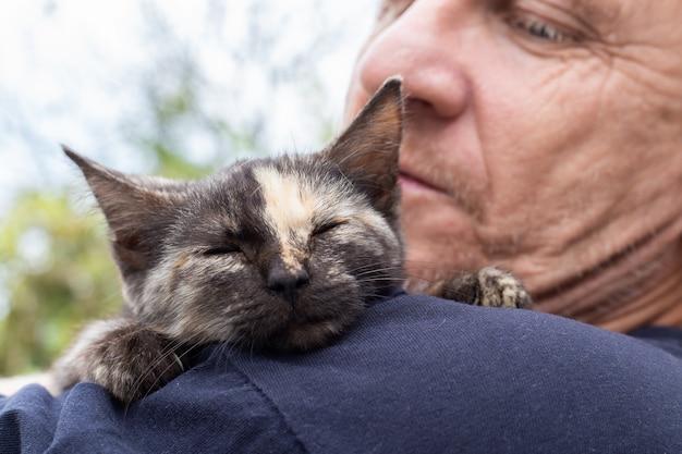 Котенок с полоской на носу спит на плече взрослого мужчины. любовь к домашним животным.
