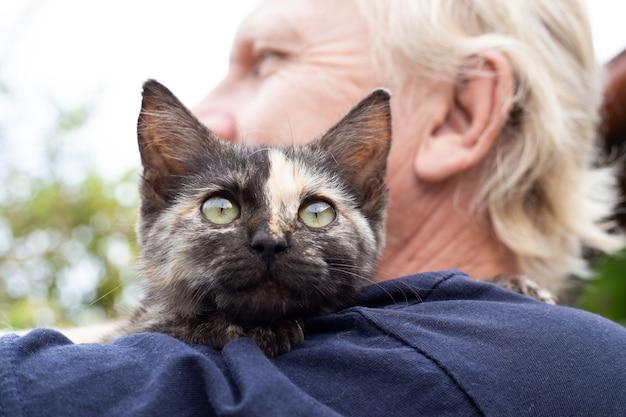 Котенок с полоской на носу на плече взрослого мужчины. любовь к домашним животным.