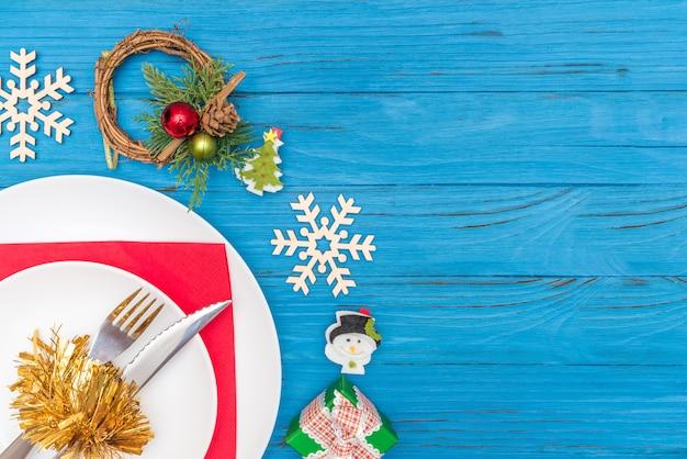 クリスマスリース木製雪片とギフトボックスで飾られた赤いナプキンに白い皿のナイフとフォーク