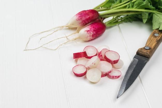 Нож с деревянной ручкой и свежий редис на белом деревянном столе.