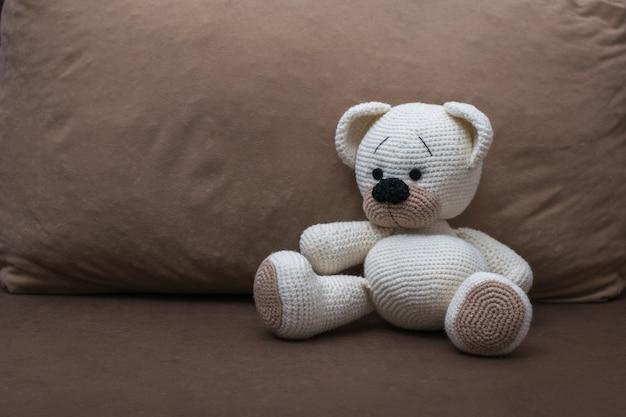 柔らかい茶色のソファの上に編まれた白いクマの子。美しいニットのおもちゃ。
