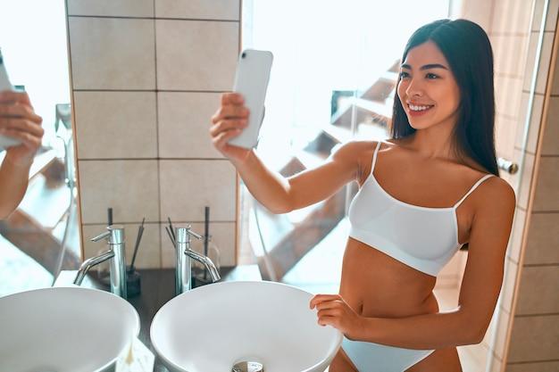 白い下着を着た韓国人女性が鏡の前のバスルームに立って自撮りします。フェイシャルとボディケア。毎朝の日課。