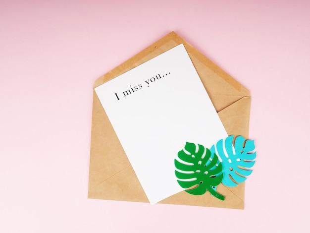 Крафт-конверт и белый лист бумаги с бумажными листьями монстера и надписью «я скучаю по тебе» вверху