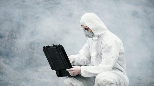 마스크와 화학 보호복을 입은 실험실 기술자가 주변의 마른 땅에서 도구 상자를 엽니다.