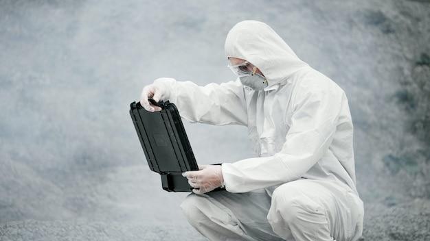 Лаборант в маске и костюме химической защиты открывает ящик с инструментами на суше