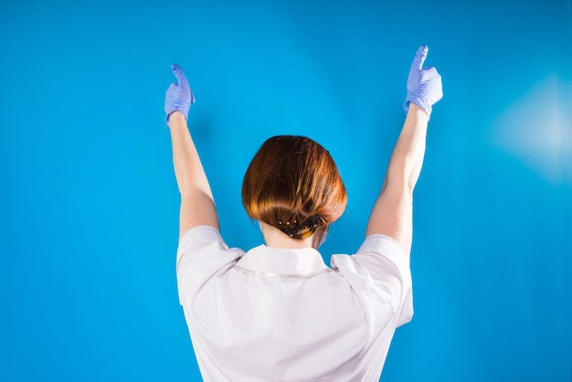 의료 유니폼과 장갑을 입은 여성이 파란색 배경에 손을 들고 있습니다