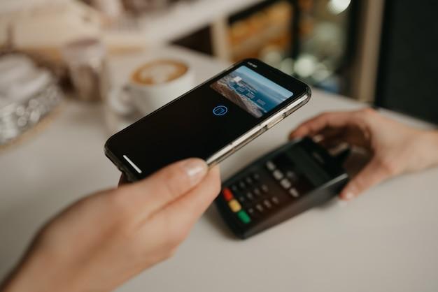 カフェで非接触型pay passテクノロジーを使用してスマートフォンでラテの支払いをしている女性。女性のバリスタがコーヒーショップのクライアントに支払うための端末を差し出します。
