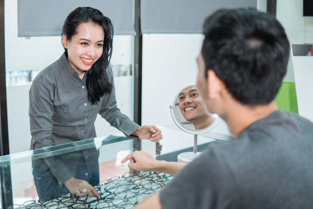 Продавец женского магазина показывает пару очков в витрине покупательнице в оптике