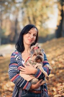 Дама гуляет в парке с маленькой собакой в солнечную погоду