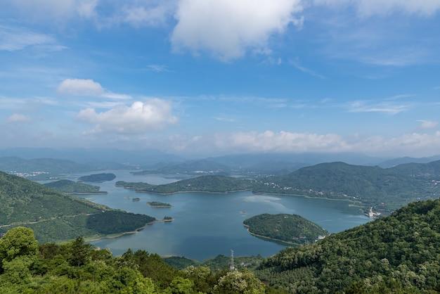 青い空と白い雲の下の森に囲まれた湖