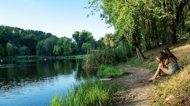モルドバのキシナウにある湖にたくさんの緑の木々が映り、2人の女の子が岸に座って葦をしています。