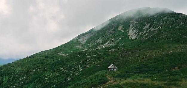 Пейзаж горной местности, покрытой травой и камнями. дом среди гор. горы покрыты туманом и облаками.