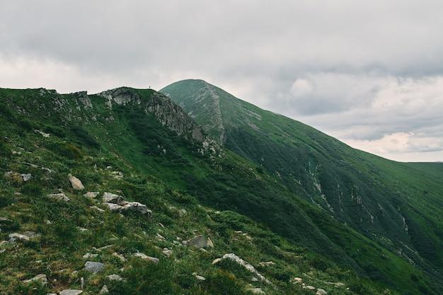 Пейзаж горной местности, покрытой травой и камнями. вдали турист, покоривший вершину горы. облачно горный пейзаж.