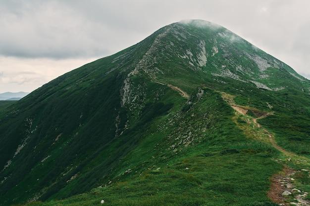 Пейзаж горной местности, покрытой травой и камнями. горы покрыты туманом и облаками. туризм, путешествия, отдых, активный образ жизни.