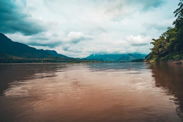 晴れた夏の日のビンロン近くの南ベトナムのメコン川のほとりの風景写真。雲の中の山。ラオスの風景。