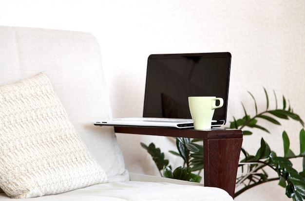 ラップトップとソファの上のお茶。ホームオフィス。